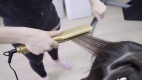 Frisören gör hårlamination i en skönhetsalong för en flicka med brunetthår Begrepp f?r h?romsorg arkivfilmer