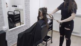 Frisören gör hårlamination i en skönhetsalong för en flicka med brunetthår Begrepp f?r h?romsorg stock video