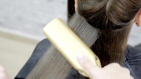 Frisören gör hårlamination i en skönhetsalong för en flicka med brunetthår close upp lager videofilmer
