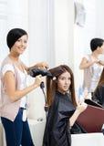 Frisören gör hårstil av kvinnan i friseringsalong Royaltyfria Bilder