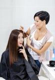 Frisören klipper hår av kvinnan i friseringsalong royaltyfri foto