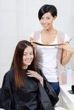 Frisören klipper hår av kvinnan i hairdresssalong royaltyfri fotografi