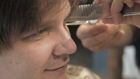 Frisören klipper hår på templet och örat till klienten i en salong Mansammanträde i frisörfåtölj, medan klippa stock video