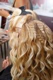 Frisören och makeupstylisten gör frisyren och makeup av bruden i skönhetsalongen Frisören krullar hår av blont G royaltyfri bild