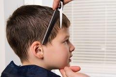 Frisören rymmer en hårkam och sax i hennes hand och gör en frisyr för pojken royaltyfria foton