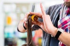 Frisören som utformar kvinnahår shoppar in Arkivfoto