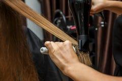 Frisören torkar hår till klienten med en hårtork arkivfoto