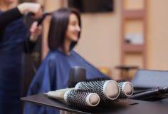 Frisören torkar hennes hår en brunettflicka i en skönhetsalong arkivfoto