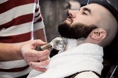 Frisörmannen rakar en klient med ett skägg i en frisersalong arkivbilder