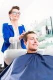 Frisörrådgivningman på frisyr i frisersalong Arkivbild