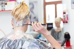 Frisörsalong Kvinna under hårfärg Arkivbild