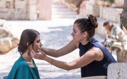 Frisörstylisten gör en frisyr för modellen, innan han skjuter, innan han skjuter på Mt Scopus i Jerusalem i Israel royaltyfri foto