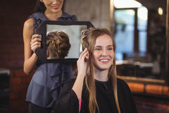 Frisörvisningkvinna hennes frisyr i spegel Royaltyfria Bilder