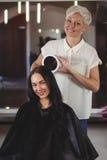 Frisörvisningkvinna hennes frisyr i spegel Arkivbild
