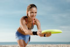 Frisbee at the beach. A young woman is playing in a frisbee at the beach. A girl in a sport wear is doing sports Royalty Free Stock Image