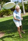 Frisbee de projection actif heureux d'homme aîné à l'extérieur Images libres de droits