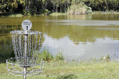 Frisbee Golf Goal by a Lake in a Park. Oakland Park, FL, USA - November 8, 2016: Easterlin Park Frisbee Golf sign on a goal post basket target by a lake. Disc royalty free stock image