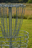 Frisbee golf hole. With basket and chains to help disc fall into basket Stock Image