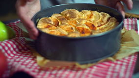 Frisch Bratapfelkuchen nahaufnahme Die gesetzten Hände backten Apfelkuchen auf Tabelle stock footage