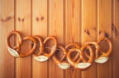 Frisch gebackene Brezeln, die an der Wäscheleine gegen hölzernes Brett hängen Hintergrund für Oktoberfest stockfotos