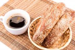 Frisch gebackene Brötchen mit indischem Sesam mit Tasse Kaffee Lizenzfreie Stockbilder