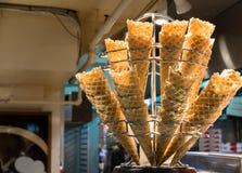 Frisch gebackene Eiscreme-Waffelkegel, die auf dem silbernen Stand sitzen Lizenzfreies Stockbild