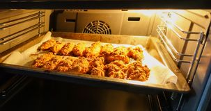 Frisch gebackene Hühnerleiste auf einem Backblech in einem elektrischen Ofen Kochen von Hühnernuggets serie lizenzfreies stockbild