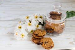 Frisch gebackene Hafermehlrosinenplätzchen und Narzisse Stockbild