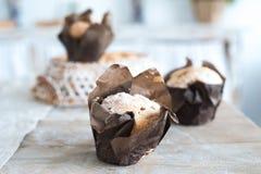 Frisch gebackene Muffins der kleinen Kuchen auf einem großen strukturierten Holztisch Selbst gemachtes Gebäck in der Pergamentnah lizenzfreie stockfotografie