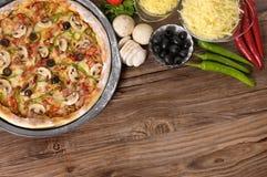 Frisch gebackene Pizza mit Bestandteilen und copyspace Stockfotos