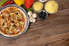 Frisch gebackene Pizza mit Bestandteilen und copyspace Stockfotografie