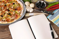 Frisch gebackene Pizza mit Kochbuch Stockbilder