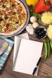 Frisch gebackene Pizza mit Kochbuch Stockbild