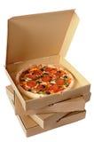 Frisch gebackene Pizza mit Stapel Lieferungskästen Stockbild