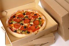 Frisch gebackene Pizza mit Stapel Lieferungskästen Stockfotos