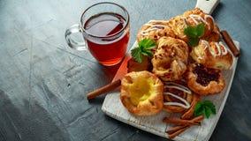 Frisch gebackene süße mini dänische klebrige Ahornpekannuß des traditionellen Gebäcks, Zimt, Apple, Himbeermischung mit heißem Stockfotos