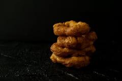 Frisch gebackene Schaumgummiringe mit Zucker pulverisieren fallendes dunkles Foto Lizenzfreie Stockfotos