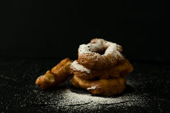Frisch gebackene Schaumgummiringe mit Zucker pulverisieren fallendes dunkles Foto Stockfoto