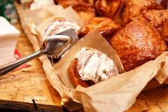 Frisch gebackene Zimtbrötchen mit den Gewürzen und Kakao, die auf Pergamentpapier füllen lizenzfreies stockbild