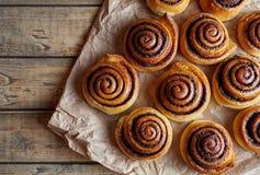 Frisch gebackene Zimtbrötchen mit den Gewürzen und Kakao, die auf Pergamentpapier füllen Süßes selbst gemachtes Gebäckweihnachtsb Lizenzfreie Stockbilder