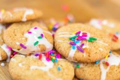 Frisch gebackene Zuckerplätzchen mit Regenbogen besprüht auf hölzernem Brett Lizenzfreies Stockfoto