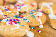 Frisch gebackene Zuckerplätzchen mit weißer dem gefärbtem Zuckerglasur und Regenbogen besprüht Stockfoto