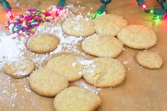 Frisch gebackene Zuckerplätzchen mit weißer dem gefärbtem Zuckerglasur und Regenbogen besprüht Stockbilder