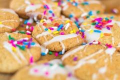 Frisch gebackene Zuckerplätzchen mit weißer dem gefärbtem Zuckerglasur und Regenbogen besprüht Lizenzfreie Stockfotos