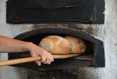 Frisch gebackenes Brot im alten timey Holzofen Lizenzfreies Stockbild