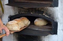 Frisch gebackenes Brot im alten timey Holzofen Lizenzfreie Stockbilder