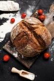 Frisch gebackenes Brot, Mehl und Tomaten auf einem hölzernen Brett auf einer Tabelle Stockbilder