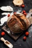 Frisch gebackenes Brot, Mehl und Tomaten auf einem hölzernen Brett auf einer Tabelle Stockbild