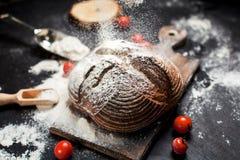 Frisch gebackenes Brot, Mehl und Tomaten auf einem hölzernen Brett auf einer Tabelle Lizenzfreies Stockfoto