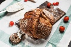 Frisch gebackenes Brot, Mehl und Tomaten auf einem hölzernen Brett auf einem Geschirrtuch auf einer Tabelle Stockfotografie